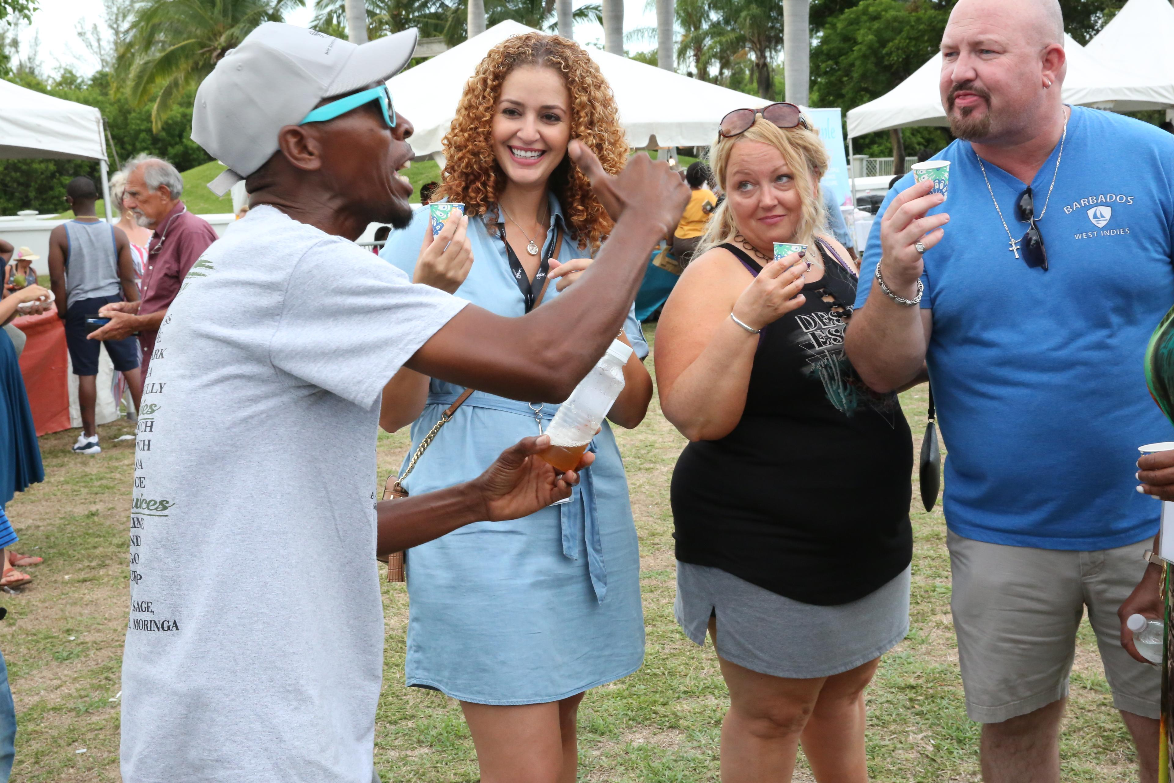 "Fenrick Russell "" Mr. Bush Tea"" shows a variety of teas ay the Goombay Summer Festival  to travel agents Steven Troy Yarborough and Amy Yarborough. Tina Lee BTO Florida looks on."