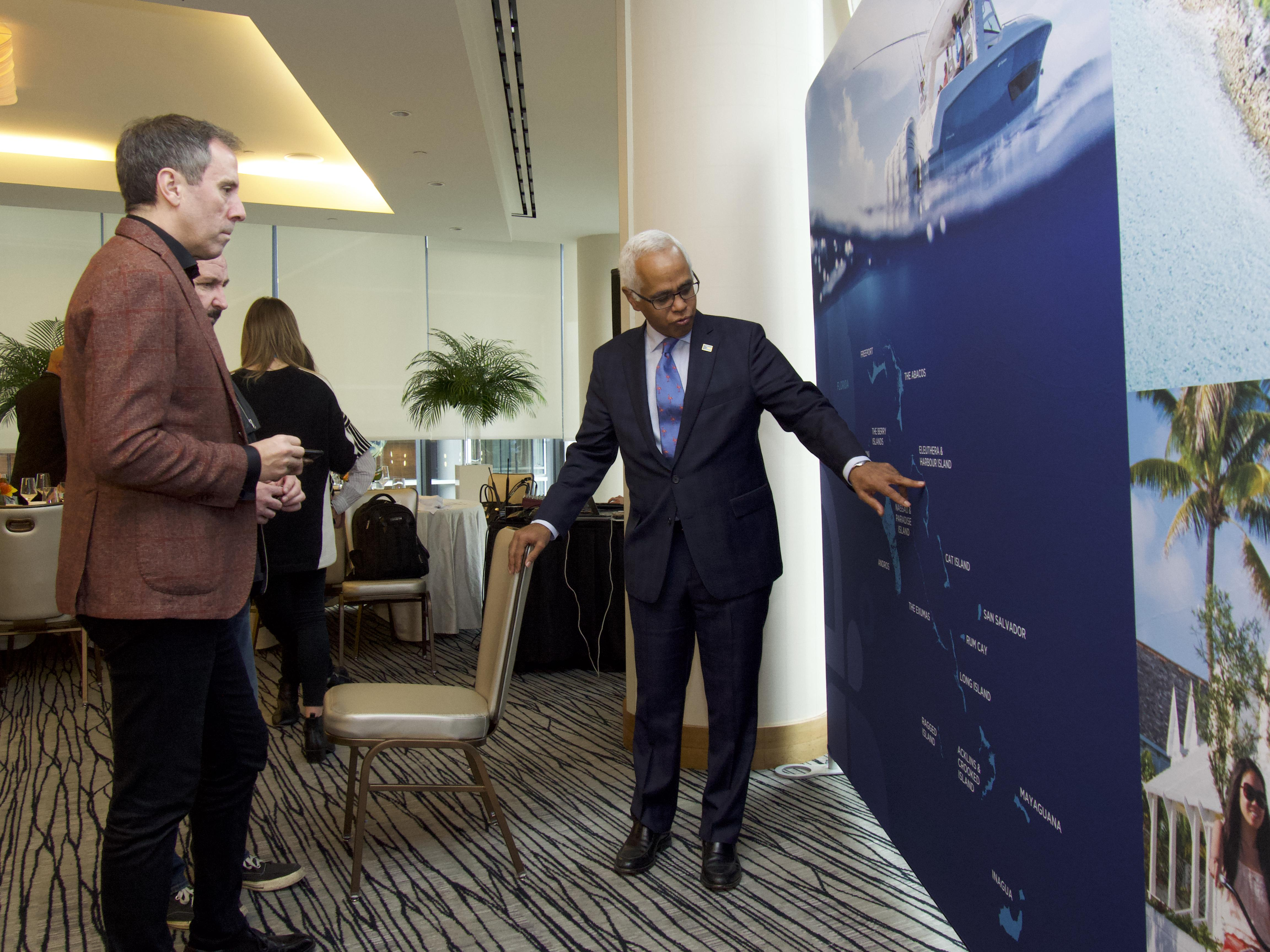 Minister educating media guests on the geography of The Bahamas at Vancouver Media event