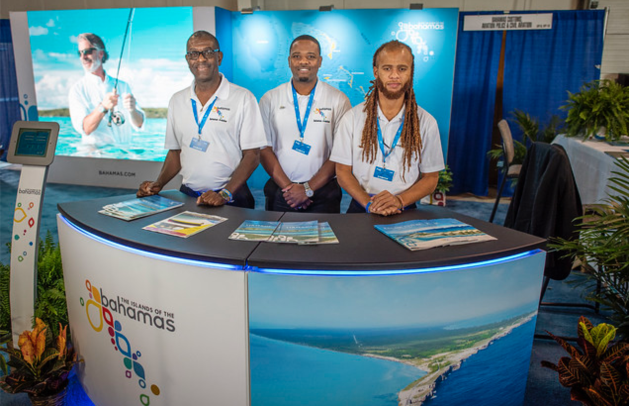1.Pictured are staff members of the Bahamas Ministry of Tourism and Aviation standing ready at its booth to answer aviators' questions, prior to EAA AirVenture Oshkosh gate opening.  From left to right are Leonard Stuart, Ahmad Williams and Aram Bethell.