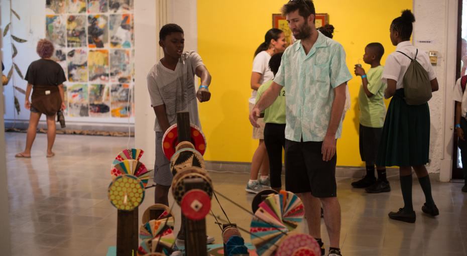 Artist Dylan Rapillard discussing Kinetic Art Sculpture - You Are Here - with a student.